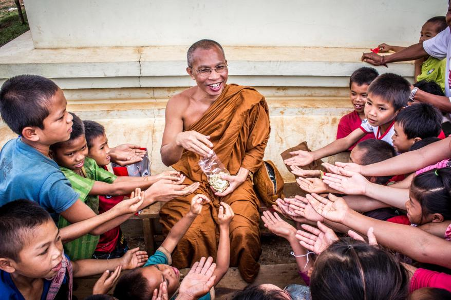 man-in-monk-dress-between-group-of-children-933620