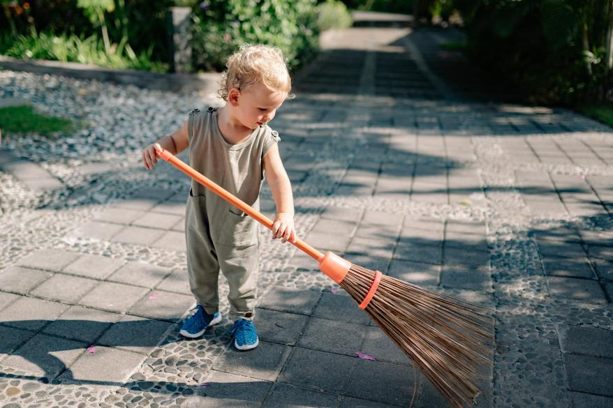 charming-child-sweeping-path-with-broom-in-summer-in-4458033
