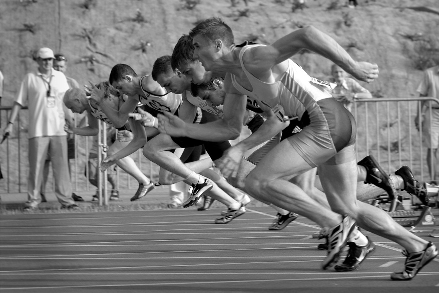 athletes-running-on-track-and-field-oval-in-grayscale-34514
