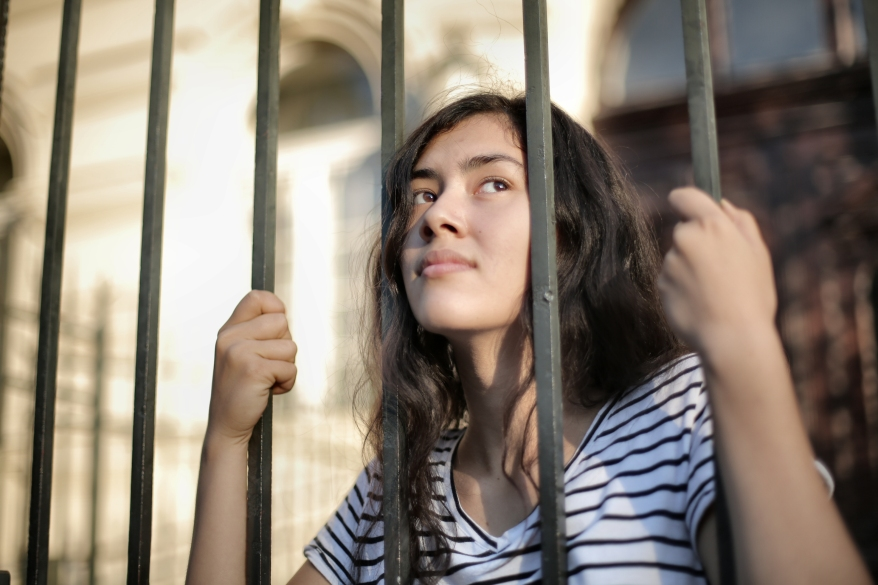 sad-isolated-young-woman-looking-away-through-fence-with-3808803
