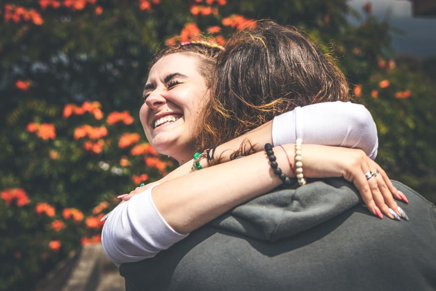 smiling-woman-hugging-another-person-2292932